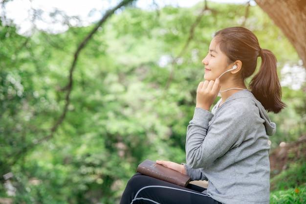 若いクリスチャンアジアの女性は、春のシーズンに公園で彼女の携帯電話で音楽の神の祝福を喜んで聴きます。