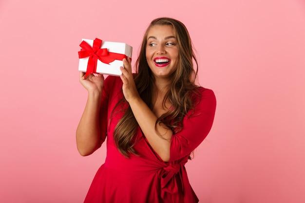 웃 고 선물 상자를 들고 빨간 드레스를 입고 젊은 통통한 여자 20 대