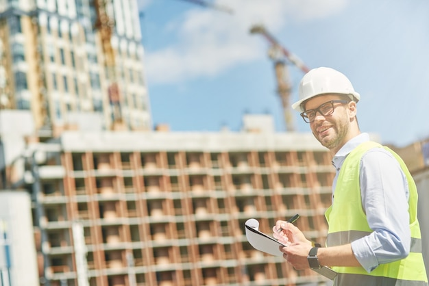 Young civil engineer or construction supervisor wearing helmet smiling at camera while inspecting
