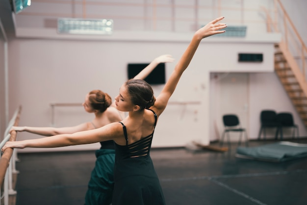 Young classic female dancers practising in the dance studio