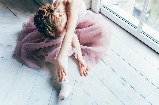 ダンスクラスの若いクラシックバレエダンサーの女の子。ピンクのチュチュスカートの美しい優雅なバレリーナは、トウシューズを履きます
