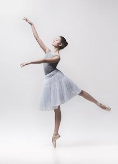 Молодой классический танцор танцует на белом фоне. проект балерины.