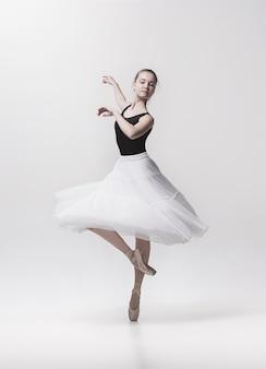 白い背景の上で踊って若いクラシックダンサー。バレリーナプロジェクト。