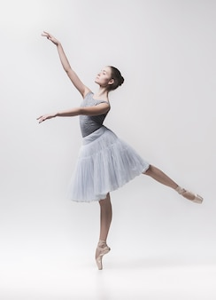 Young classical dancer dancing on white background. ballerina project.