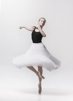 Young classical dancer dancing on white