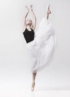 白い背景で隔離の若いクラシックダンサー。