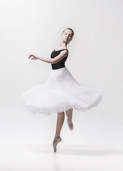 Young classical dancer isolated on white.