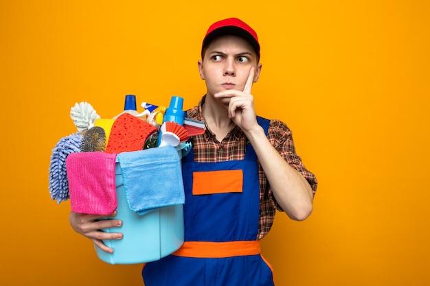 オレンジ色の壁に分離されたクリーニングツールのバケツを保持している制服と帽子を身に着けている若いクリーニング男