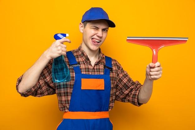 オレンジ色の壁に隔離されたモップヘッドと制服とキャップ保持洗浄剤を身に着けている若いクリーニング男