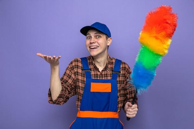 파란색 벽에 격리된 피피다스트레를 들고 유니폼을 입고 모자를 쓴 젊은 청소부