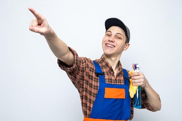 制服を着た若い掃除人と白い壁に隔離された洗浄剤でぼろきれを保持しているキャップ