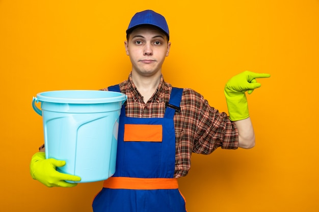 유니폼을 입고 모자를 쓴 젊은 청소부, 장갑을 끼고 복사공간이 있는 주황색 벽에 격리된 양동이를 들고