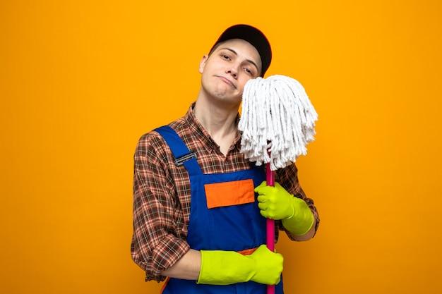 주황색 벽에 걸레를 들고 장갑을 끼고 유니폼을 입고 모자를 쓴 젊은 청소부