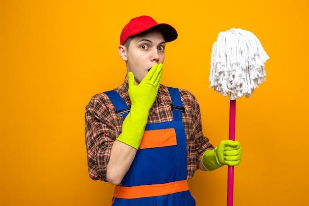 オレンジ色の壁に隔離されたモップを保持している手袋と制服とキャップを身に着けている若い掃除人