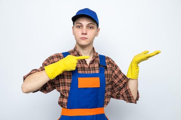 복사 공간이 있는 흰 벽에 장갑을 끼고 유니폼과 모자를 쓴 젊은 청소부