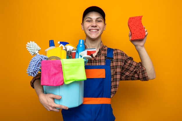 Young cleaning guy wearing uniform and cap holding bucket of cleaning tools with sponge isolated on orange wall