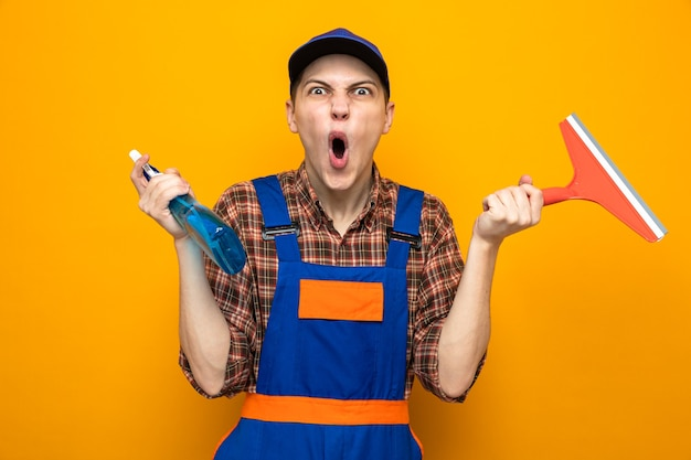 Giovane addetto alle pulizie che indossa l'uniforme e il berretto che tiene il detergente con la testa del mocio isolata sul muro arancione