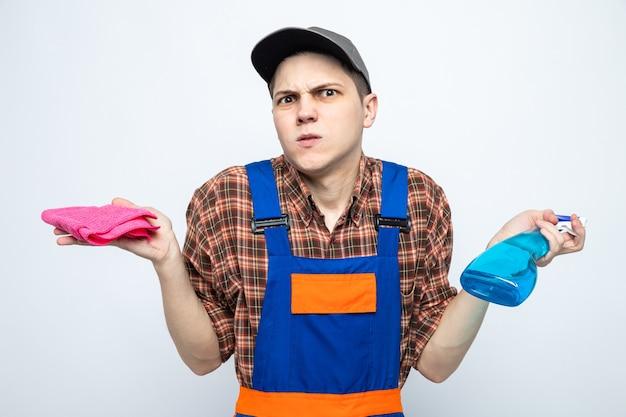Giovane addetto alle pulizie che indossa l'uniforme e berretto che tiene uno straccio con detergente isolato su parete bianca