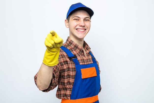 Young cleaning guy wearing uniform and cap with gloves isolated on white wall