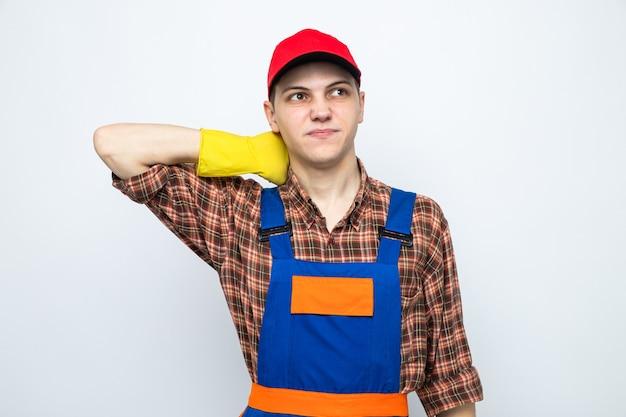 Giovane ragazzo delle pulizie che indossa uniforme e berretto con guanti isolati su muro bianco