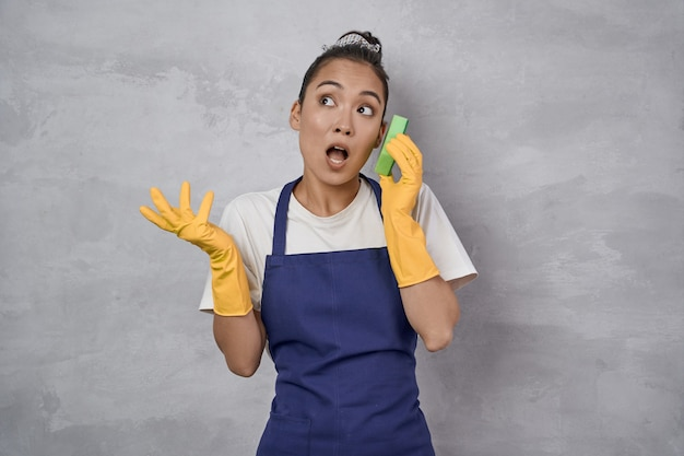 유니폼을 입고 고무 장갑을 끼고 주방 스펀지를 가지고 노는 젊은 청소부, 회색 벽에 서서 휴대폰 통화를 하는 척. 스튜디오 촬영. 하우스키핑, 청소 서비스