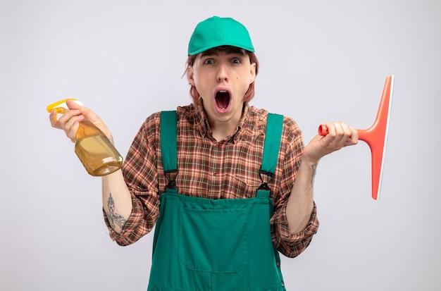 格子縞のシャツのジャンプスーツと帽子を持った若い掃除人が掃除スプレーとモップを持って白い壁の上に立って驚いた