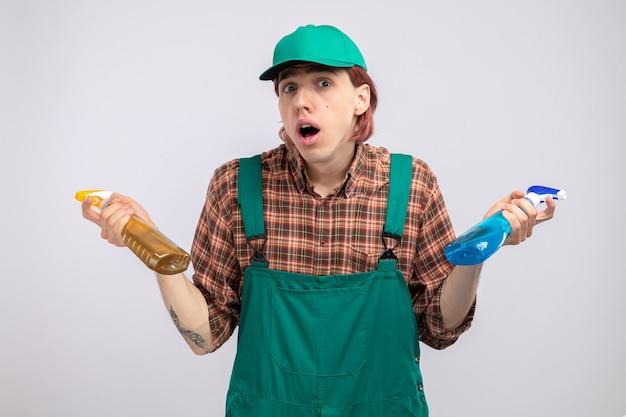 격자 무늬 셔츠 점프수트를 입은 젊은 청소부와 청소 스프레이 병을 들고 있는 모자는 흰 벽 위에 서 있는 어깨를 으쓱하며 혼란스러워한다