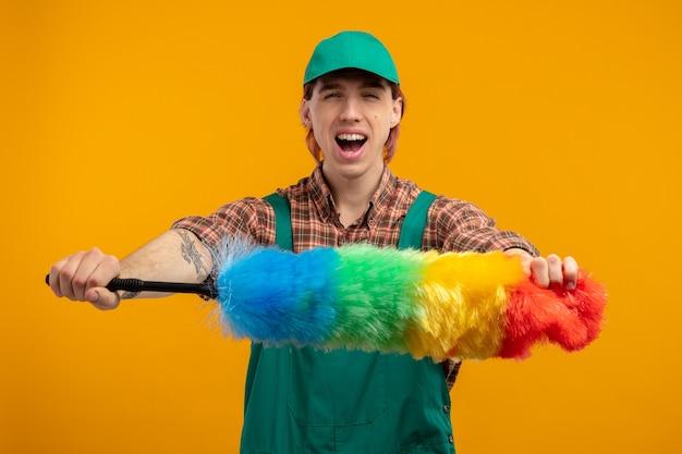 オレンジ色の壁の上に立って幸せで興奮してカラフルなダスターを保持している格子縞のシャツのジャンプスーツと帽子の若い掃除人