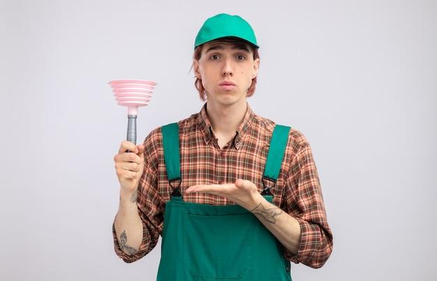 체크무늬 셔츠 점프수트를 입은 젊은 청소부와 플런저를 들고 있는 모자를 쓰고 흰 벽 위에 자신감을 보이는 손으로 팔을 내밀고 있다