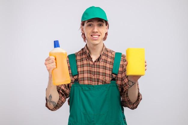 격자 무늬 셔츠 점프수트를 입은 젊은 청소부와 스폰지와 병을 들고 있는 모자, 웃는 얼굴로 보이는 청소 용품
