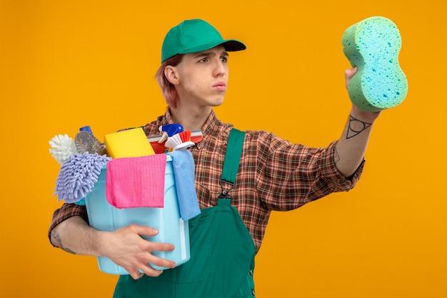 格子縞のシャツのジャンプスーツとキャップを保持しているスポンジとバケツを持った若い掃除人が、オレンジ色の上に立って掃除の準備ができている深刻な顔を脇に見ている掃除道具を持っています