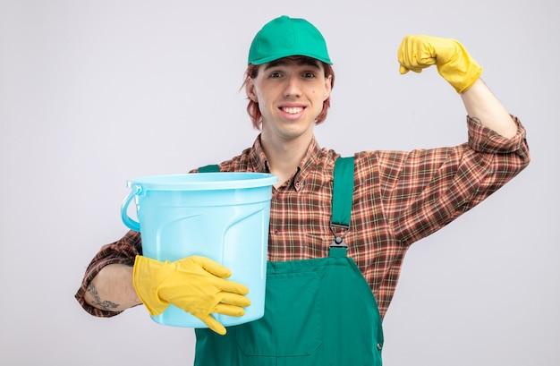 격자 무늬 셔츠 점프수트를 입은 젊은 청소부와 고무 장갑을 끼고 양동이를 들고 흰 벽 위에 서 있는 승자처럼 자신감 있게 주먹을 들고 있는 청소부