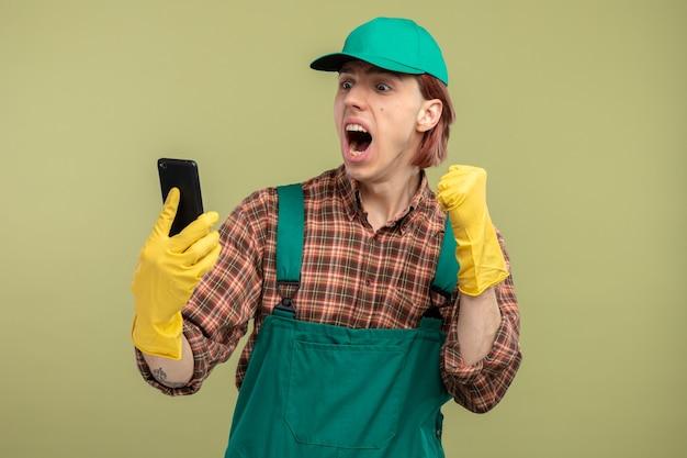 格子縞のシャツのジャンプスーツとゴム手袋を着用して彼の携帯電話を見て幸せで興奮した握りこぶしを身に着けている若い掃除人