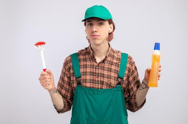 Giovane uomo delle pulizie in tuta da camicia a quadri e berretto che tiene in mano una spazzola per la pulizia e una bottiglia con prodotti per la pulizia che sembrano sorridenti fiduciosi