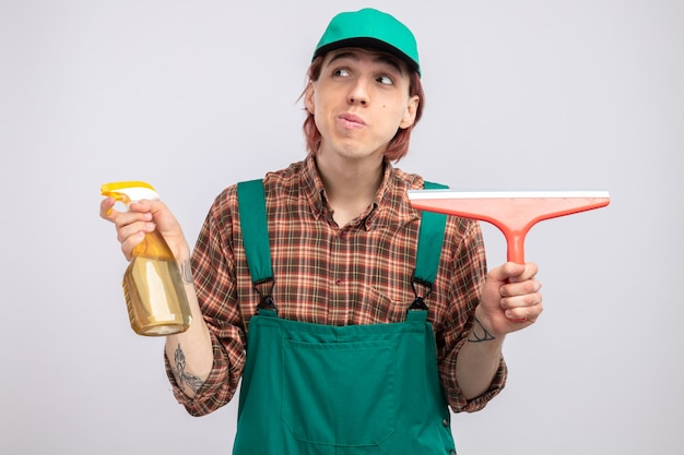 Young cleaning man in plaid shirt jumpsuit and cap holding cleaning spray and mop looking aside smiling confused standing on white