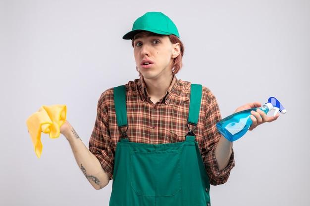 Giovane uomo delle pulizie in tuta a quadri e berretto che tiene in mano uno straccio e uno spray per la pulizia che sembra sorpreso e confuso