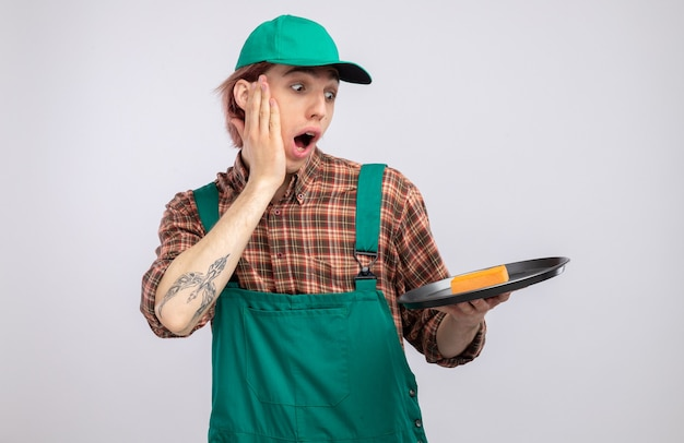 Young cleaning man in plaid shirt jumpsuit and cap holding tray and sponge looking at them amazed and surprised standing over white wall