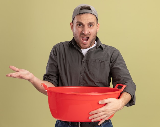 緑の壁の上に立って腕を上げて怒って不満を持って洗面器を保持しているカジュアルな服と帽子を身に着けている若い掃除人