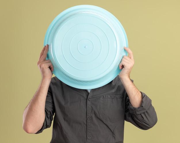 緑の壁の上に立っているその後ろに顔を隠している洗面器を保持しているカジュアルな服と帽子を身に着けている若い掃除人