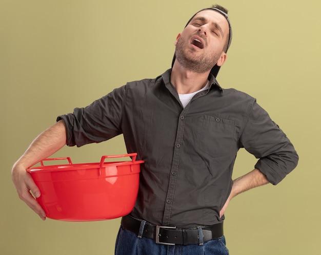 緑の壁の上に立って疲れて退屈そうに見える洗面器を保持しているカジュアルな服と帽子を身に着けている若い掃除人