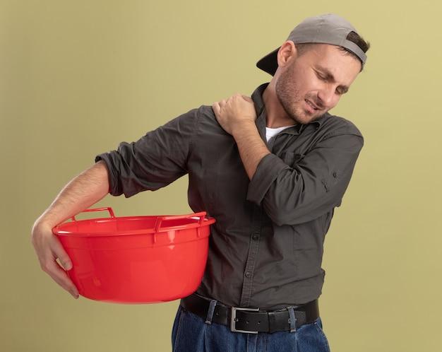 緑の壁の上に立って疲れて過労を感じて肩に触れて洗面器を保持しているカジュアルな服と帽子を身に着けている若い掃除人