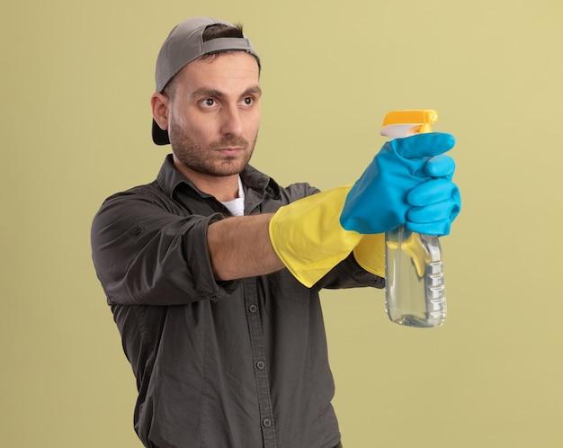 녹색 벽 위에 서 심각한 얼굴로 옆으로 찾고 스프레이 병을 목표로 고무 장갑에 캐주얼 옷과 모자를 착용하는 젊은 청소 남자