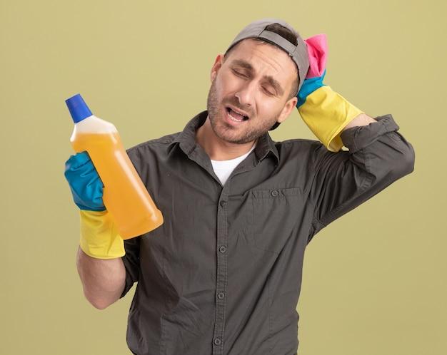 Молодой уборщик в повседневной одежде и кепке в резиновых перчатках держит бутылку с чистящими средствами и тряпкой, выглядит смущенным и очень взволнованным, стоя у зеленой стены