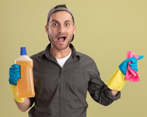 Молодой уборщик в повседневной одежде и кепке в резиновых перчатках держит бутылку с чистящими средствами и тряпкой, выглядит счастливым и взволнованным, стоя у зеленой стены