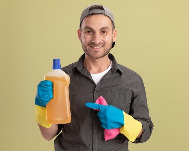 Молодой уборщик в повседневной одежде и кепке в резиновых перчатках держит бутылку с чистящими средствами и тряпкой, выглядит счастливым и позитивно улыбается, стоя над зеленой стеной