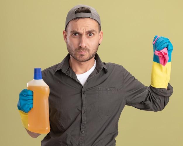 Молодой уборщик в повседневной одежде и кепке в резиновых перчатках держит бутылку с чистящими средствами и тряпкой, глядя с сердитым лицом, стоящим над зеленой стеной