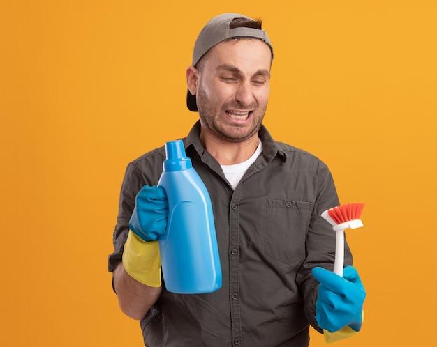 오렌지 벽 위에 서있는 혐오스러운 표정으로 브러시를보고 청소 용품으로 청소 브러시와 병을 들고 고무 장갑에 캐주얼 옷과 모자를 착용하는 젊은 청소 남자