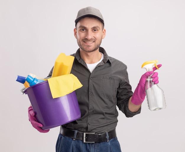 白い壁の上に立っている幸せそうな顔で笑顔に見えるクリーニングツールとスプレーボトルとバケツを保持しているゴム手袋でカジュアルな服とキャップを身に着けている若いクリーニング男