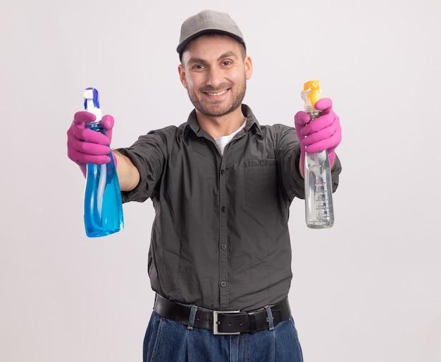 白い壁の上に元気に立って笑顔に見えるスプレーボトルを保持しているゴム手袋でカジュアルな服とキャップを身に着けている若い掃除人