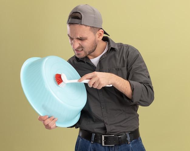 Giovane uomo delle pulizie che indossa abiti casual e berretto tenendo il bacino e la spazzola per la pulizia che sembra confuso e dispiaciuto in piedi sopra la parete verde